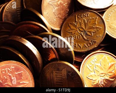 Closeup of Canadian and American copper pennies with the focus on a 1980 Canada penny - Stock Photo
