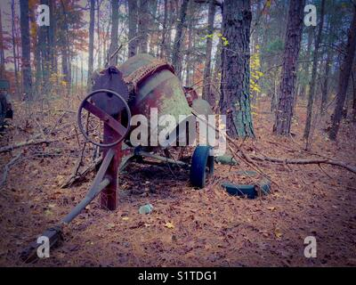 Old cement mixer in woods on farm - Stock Photo