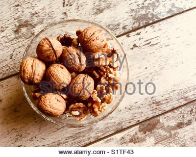 Walnuts presented in a glass bowl - copy space provided - Stock Photo