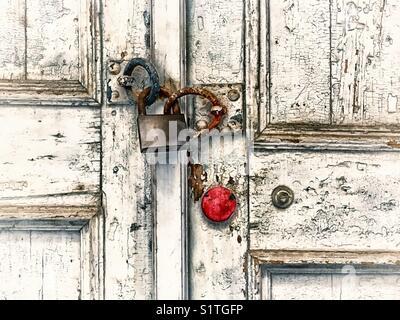 Old wooden door locked with rusty padlock - Stock Photo
