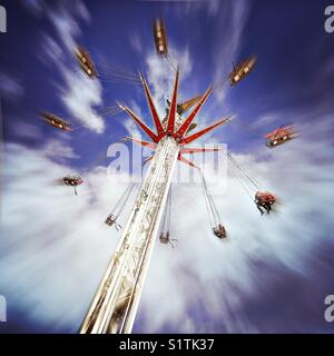 Two people ride the StarFlyer fairground ride as it spins against a blue and white cloudy sky on a sunny day. - Stock Photo