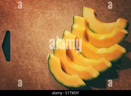 Slices of cantaloupe melon arranged nicely on a brown cutting board - Stock Photo