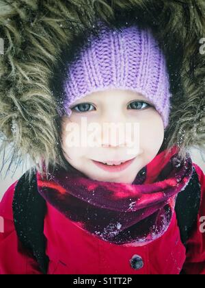 Portrait of 5 year old girl wearing snowsuit with furry hood outside in the snow - Stock Photo