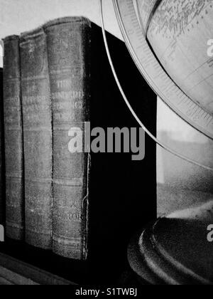 Black and white photo of antique books and globe - Stock Photo