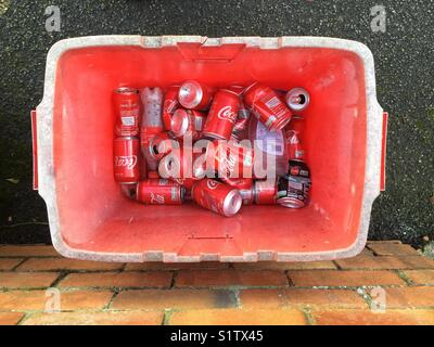 Empty Coca Cola cans in a red recycling container. Builth Wells, Powys, Wales, UK. - Stock Photo