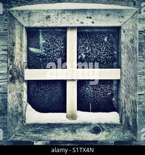 Small square window on a chicken coop with frost covered glass and snow on wooden frame - Stock Photo