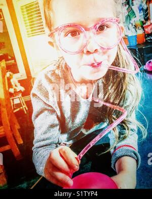 5 year old girl drinking water with a curly, crazy pink straw that runs around face like eyeglasses - Stock Photo