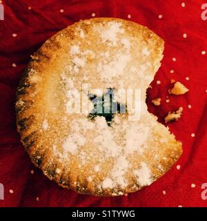 A Christmas mince pie with a bite taken out - Stock Photo
