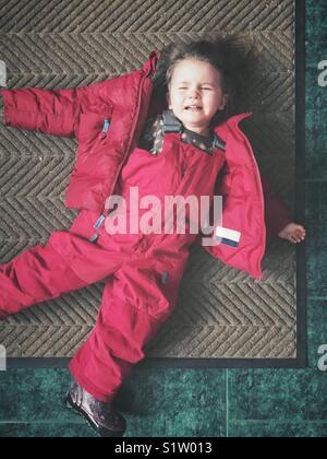 Toddler girl having a temper tantrum in pink snowsuit on doormat - Stock Photo