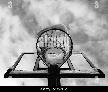 Snow covered basketball hoop. In black and white. - Stock Photo