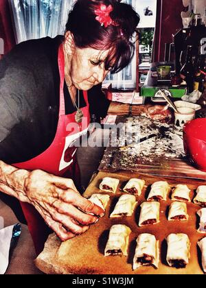 Elderly woman making sausage rolls - Stock Photo