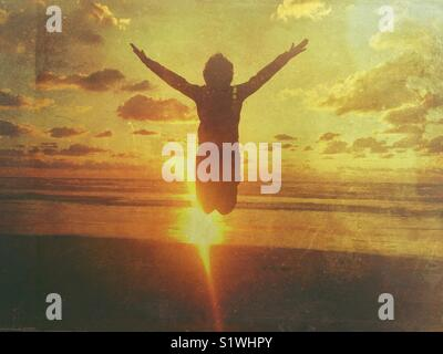 Boy jumping with arms outstretched in the beach at sunset - Stock Photo