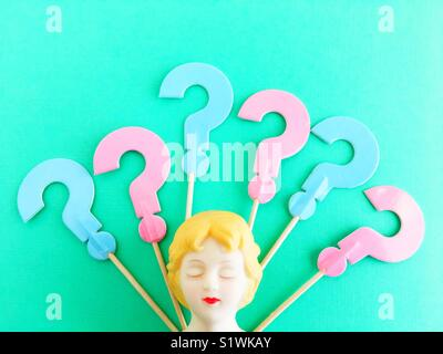 A doll head with eyes closed and question marks. - Stock Photo