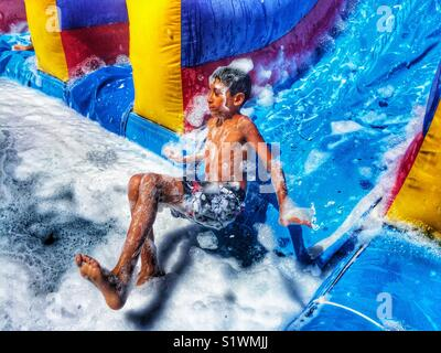 Boy sliding down a water slide with soap - Stock Photo
