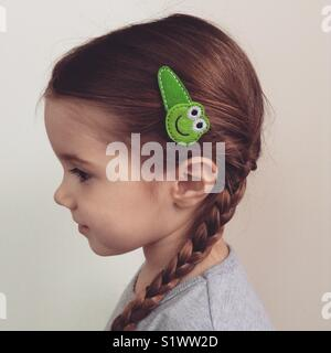 Frog hairclip little girl wearing braids happy smile profile picture - Stock Photo