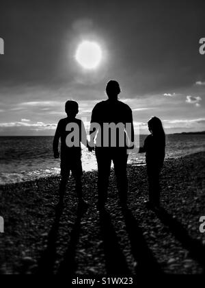 A mother/wife/lone parent holds the hands of (her?) 2 children as they stand on a beach & gaze into the bright light/sunshine(?) - Stock Photo