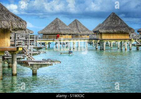 Out rigger canoe paddling around the bungalows on the island of Bora-Bora, French Polynesia in the South Pacific - Stock Photo