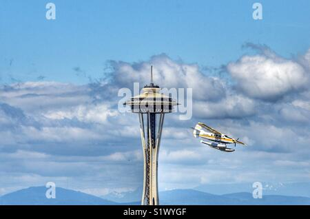 Seaplane from Kenmore air flying past the space needle in Seattle Washington on it's landing approach to Lake Union - Stock Photo