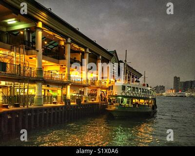 A Star Ferry at Central Pier 7 on Hong Kong Island at dusk waits to take passengers across Victoria Harbour - Stock Photo