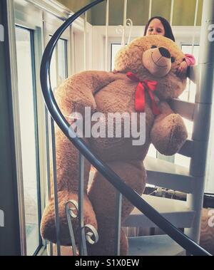 Little girl with giant oversized brown stuffed teddy bear on spiral staircase - Stock Photo