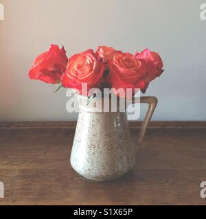 Orange red roses in a pitcher - Stock Photo