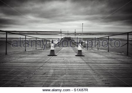 Black and white image of jetty over beach disappearing into distance on a dull day beach scene - Stock Photo