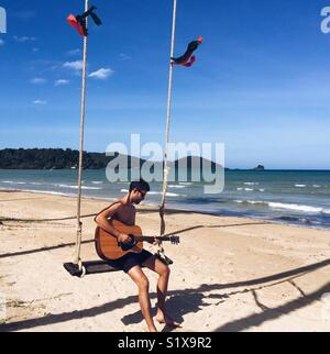 A man plays guitar while sitting on a swing enjoying the beach and sea while on an island, Koh Mak, Thailand - Stock Photo