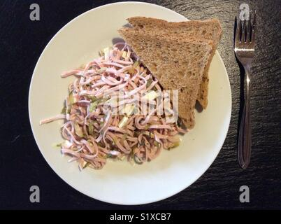 high angle view on traditional Bavarian sausage and cheese salad, whole grain bread, Bavaria, Germany, Europe - Stock Photo