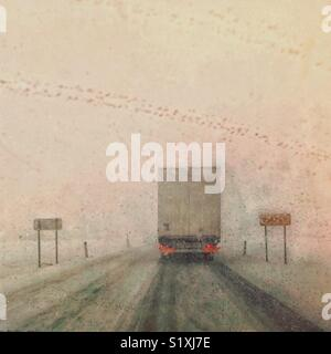 Car driving in heavy snow. A front window view of bad weather conditions - Stock Photo
