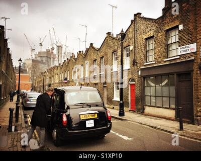 A London taxi, a black cab, drops off a passenger near Waterloo Station in London February 2018. - Stock Photo