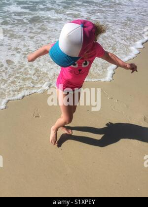 Playful summer fun as young girl runs from waves at beach. Girl in pink plays at waters edge on sunny summer day. - Stock Photo