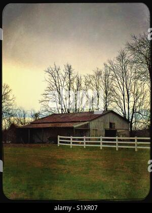White plank fence leads to old wooden barn with rusty tin roof. - Stock Photo