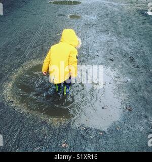 Jumping in muddy puddles.  Black Park, Buckinghamshire, UK - Stock Photo
