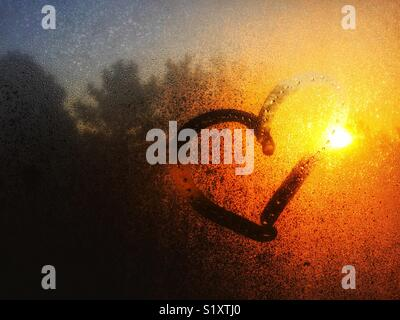 Morning sunlight on through condensed water on window with a heart drawn on it - Stock Photo