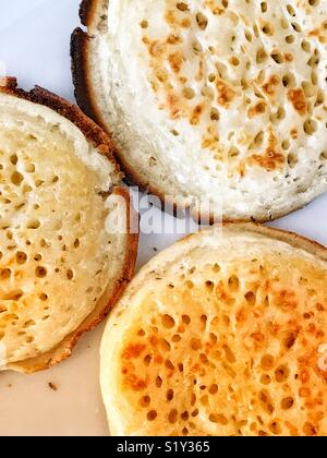 Three buttered, toasted English crumpets. - Stock Photo