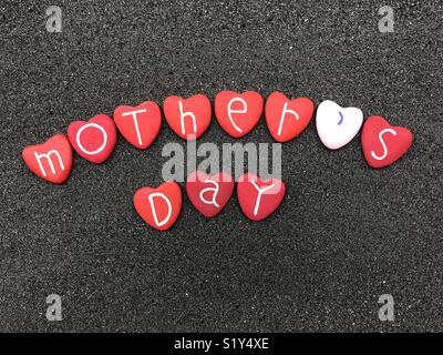 Mother's Day, red herart stones composition over original black volcanic sand - Stock Photo