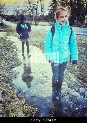 Two girls standing and walking on partially frozen water in a roadside ditch - Stock Photo