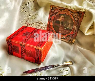 Still life antique arrangement of a silver photo frame, a silver letter opener and a book of Aristotle's Works - Stock Photo