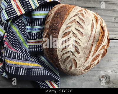 Freshly baked loaf of sourdough bread on table. - Stock Photo