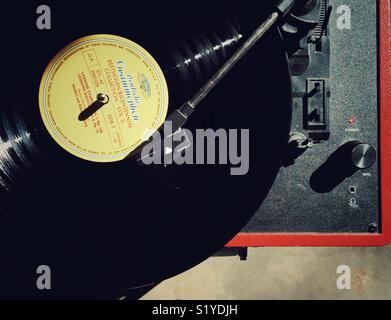 Bright sunlight shines on vintage record player with dusty record