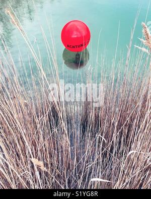 A red balloon with the message 'Achtung' floating on the surface of a pond, with reeds and weeds - Stock Photo