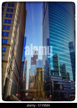 """Chicago elevated """"el"""" train passes through the Chicago Loop on its elevated track, though it is dwarfed by massive skyscrapers, including the Wills """"Sears"""" Tower. - Stock Photo"""