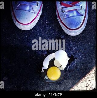 White and pink sneakers and a broken egg in a parking lot - Stock Photo