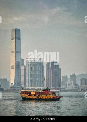 The 'Wing On Travel', a double decker Chinese junk, carrying tourists on a sightseeing cruise on Victoria Harbour at twilight, in front of the ICC, Hong Kong's tallest skyscraper, in West Kowloon