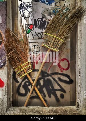 Traditional Chinese brooms and graffiti, Sai Ying Pun, Hong Kong Island - Stock Photo