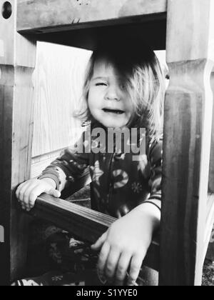 Black and white image of toddler girl crying under a wooden stool - Stock Photo