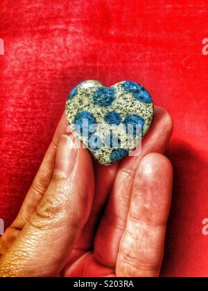 Hand holding blue spotted K2 stone heart against red background - Stock Photo