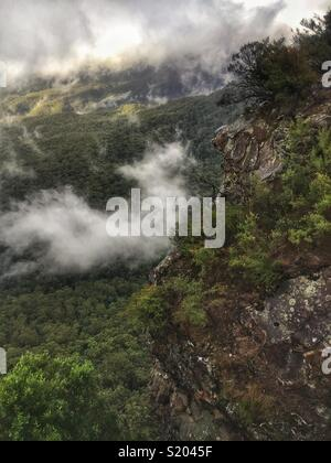 Low cloud swirls in the Jamison Valley below the sandstone cliffs of Elysian Rock Lookout, Leura, Blue Mountains National Park, NSW, Australia - Stock Photo