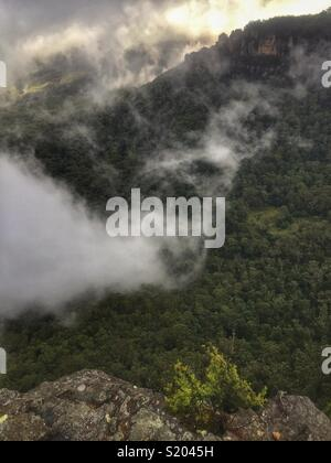 Low cloud swirls in the Jamison Valley below the sandstone cliffs from Elysian Rock Lookout to The Three Sisters, Blue Mountains National Park, NSW, Australia - Stock Photo