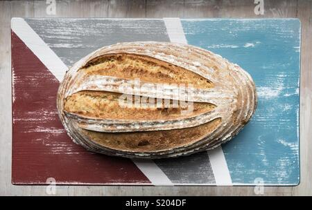 Freshly baked sourdough loaf of bread seen from above on distressed painted wooden board - Stock Photo
